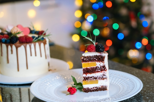 Piece of homemade christmas cake whis fruit. happy new year and merry christmas background. winter decorations over dark background with defocus xmas tree light. selective focus.