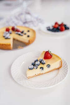 Piece of homemade christmas winter berry cheesecake on a white plate