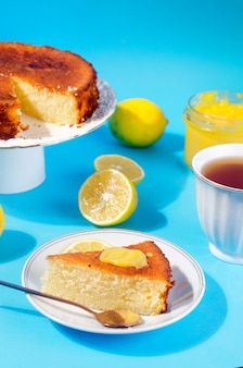 Piece of homemade freshly baked sponge cake on plate, lemon kurd in a glass jar with spoon, whole and sliced fresh lemons on plate over blue background with shadows. copy space. hard light