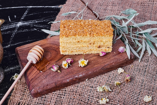 A piece of homemade honey cake with dried flowers and honey spoon on wool tablecloth.