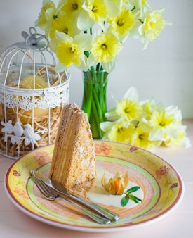 Piece of honey cake in a plate next to vase with daffodils