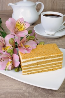Piece of honey cake with a cup of coffee on a table with a flower