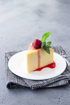 A piece of japanese cotton cheesecake with mint and strawberry.