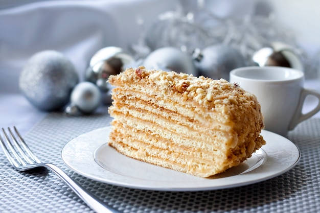 Piece of layer cake on a plate with christmas balls