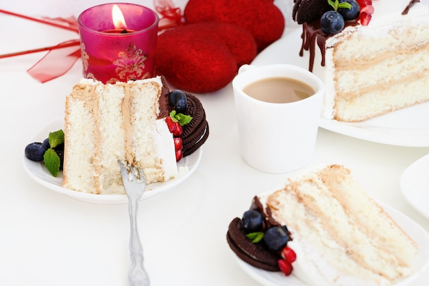 Piece of layer cake with fresh berries, cream cheese and chocolate biscuits.