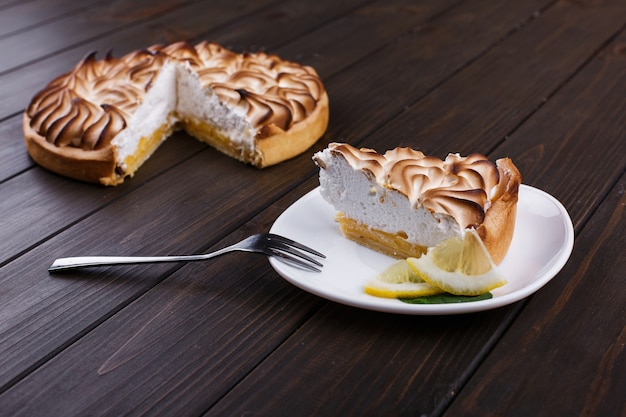 Piece of lemon pie with white cream served on white plate