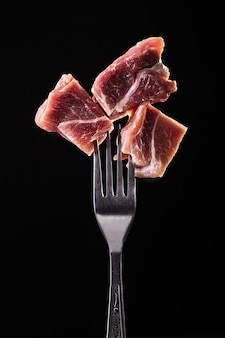 Piece of meat on a fork isolated on black.