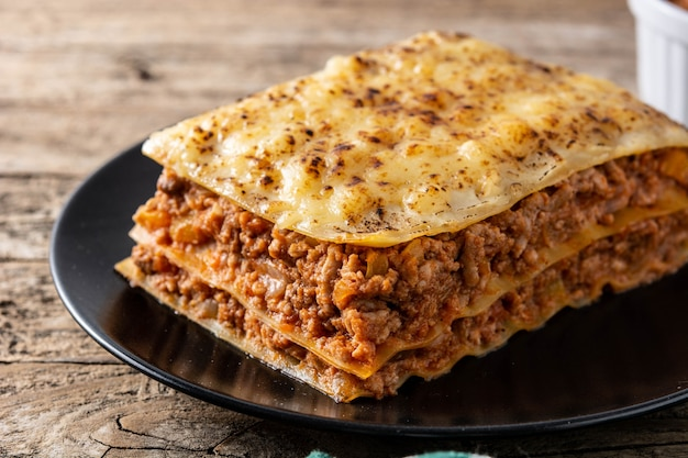 Piece of meat lasagna on black plate on wooden table