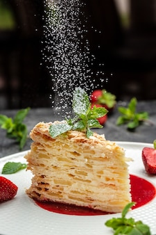 Piece of napoleon cake. creamy vanilla swith cream, apples and strawberry jam decorated mint. layered baked pie with powdered sugar in a freeze motion of a cloud of powder midair