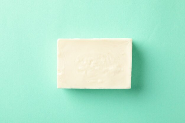 Piece of natural handmade soap on mint background