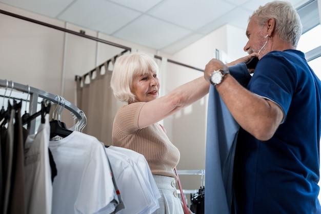 一つの忠告。愛らしい白髪の女性が、夫の胸に近づけて意見を待っている間、夫のためにプルオーバーを選ぶ