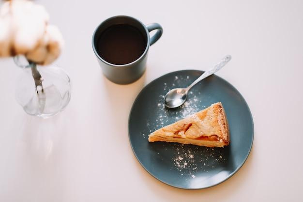 Кусок яблочного пирога на тарелке с чашкой кофе на белом столе