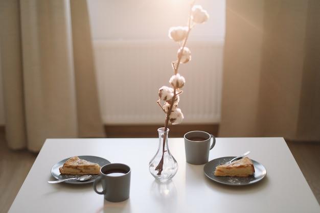 Кусок яблочного пирога на тарелке с чашкой кофе