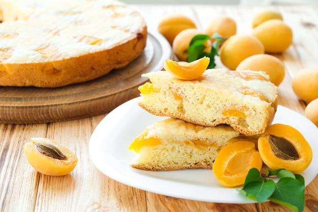 木の板の背景にフルケーキとアプリコットフルーツとプレート上のアプリコットパイの作品。休日のおやつの簡単レシピ。古典的なレシピによる自家製ベーカリー。ビーガンデザート、グルテンオフ、無糖。