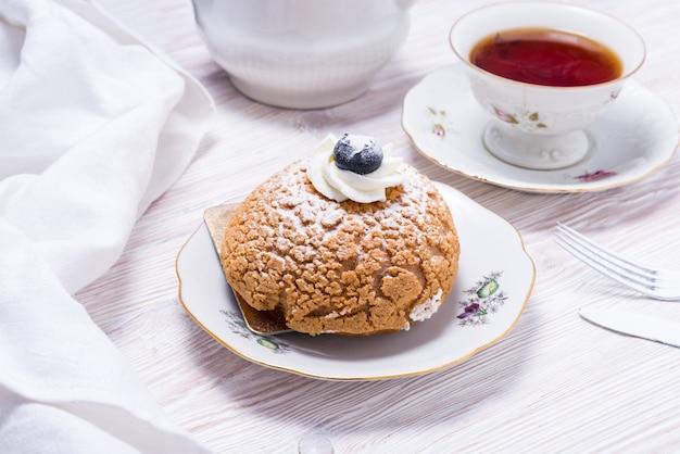 나무 배경에 신선한 딸기와 차 한 잔으로 장식된 베리 케이크 조각
