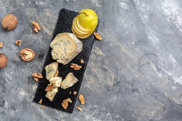 Кусок сыра с голубой плесенью данаблу, горгонзола, рокфор с грушей и грецкими орехами. баннер, меню, место рецепта для текста, вид сверху.