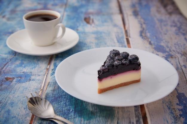 木の白いプレートにブルーベリーチーズケーキの一部
