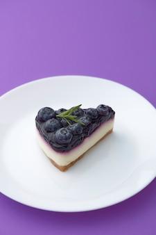 紫の背景の白いプレートにブルーベリーチーズケーキの一部