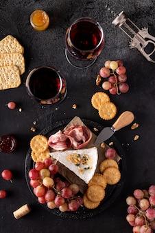 Кусок сыра бри с виноградом, крекерами и красным вином
