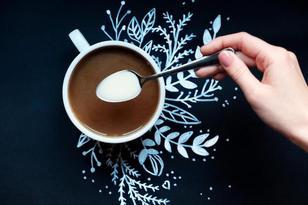新年を飾った黒い背景の上のケーキとコーヒーのカップ。白い雪の結晶を描いた。