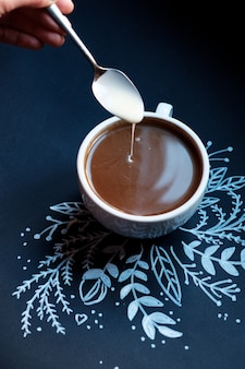 Кусок торта и чашка кофе на черном фоне украшены новым годом. окрашенная белая снежинка.