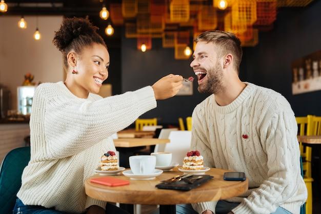 Кусок пирога. заботливая красивая кудрявая подруга дарит мужу кусок торта, сидя в кафе