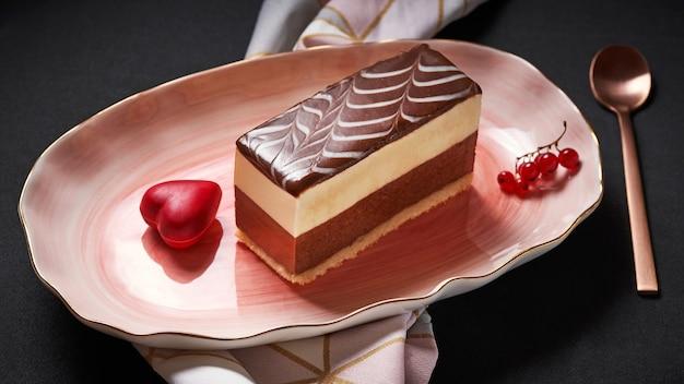 Кусок торта, покрытый шоколадной глазурью с клюквой на розовой тарелке