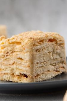 Кусок пирога наполеон на голубой плите на мраморной предпосылке, конце вверх по взгляду. традиционный десерт millefeuille с слоеным тестом и заварным кремом, копией пространства. вертикальное фото. фото для меню пекарни.