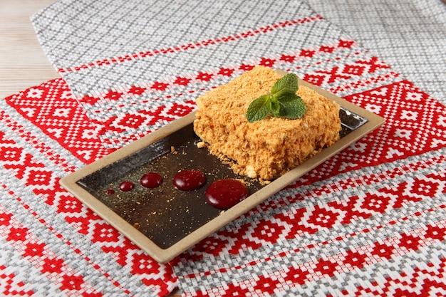 Кусок торта наполеон на коричневой тарелке на ткани с национальным белорусским орнаментом.