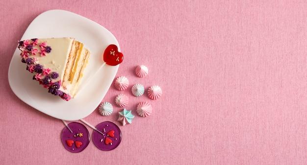 Кусок торта на тарелке на розовом фоне