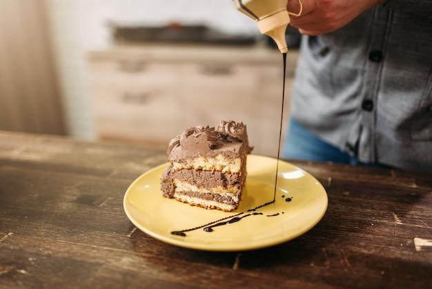 Кусок торта на тарелке, украшение шоколадным соусом.