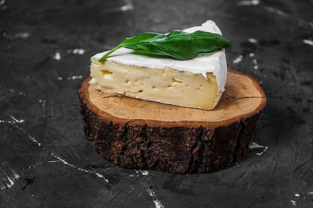 木の板と暗い表面にバジルとカマンベールチーズのかけら