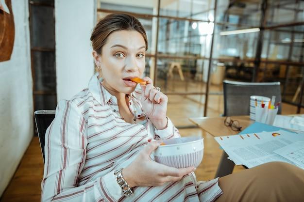 Кусок моркови. беременная зеленоглазая женщина кусает кусочек моркови после работы в офисе