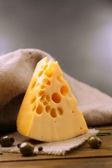 Кусок сыра на тарелке с зелеными оливками, на деревянном столе