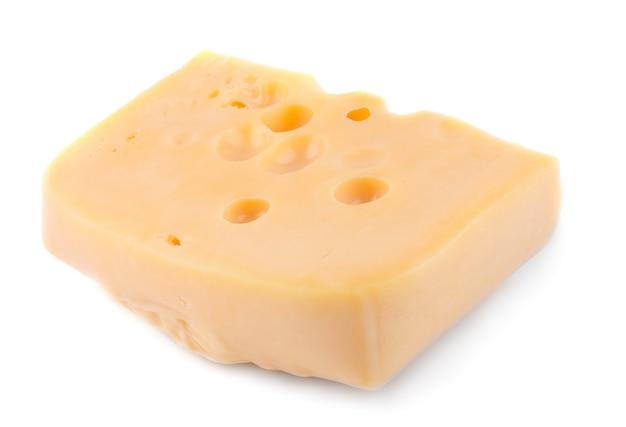 Кусок сыра с большими отверстиями желтого цвета на белом изолированном фоне