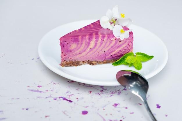 Кусок чизкейка с черникой на белой тарелке на белом фоне крупным планом