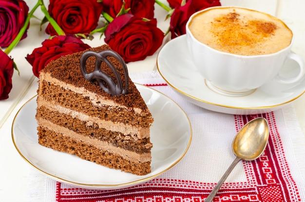 チョコレートケーキ、カプチーノ、テーブルの上の花。