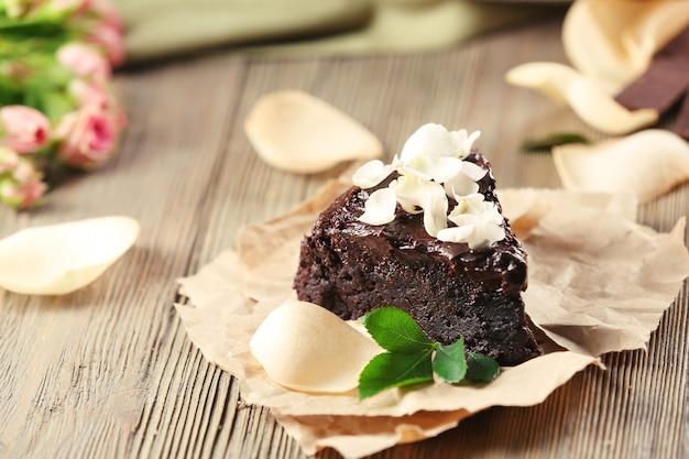 갈색 나무 테이블에 꽃으로 장식된 초콜릿 케이크 조각