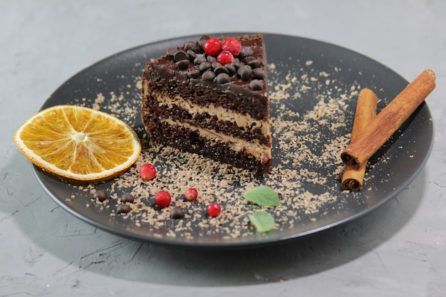 Кусок шоколадного торта на черной тарелке с ягодами и листьями мяты