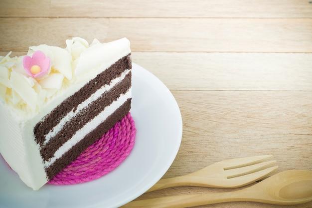 木製の背景に花とチョコレートケーキのピース