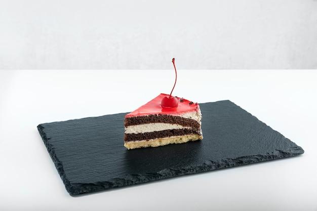 Кусок шоколадного торта с вишней мараскино. вид сбоку на кусок торта на черной тарелке.