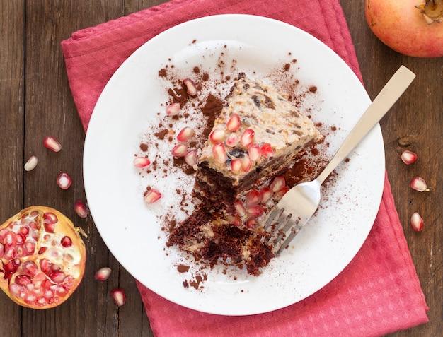 Кусок шоколада, торта грецкого ореха и чернослива на тарелке сверху