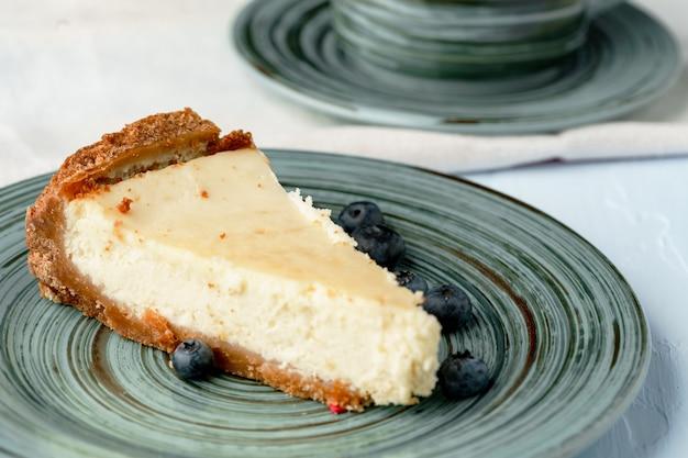 緑のプレートに古典的なチーズケーキの作品