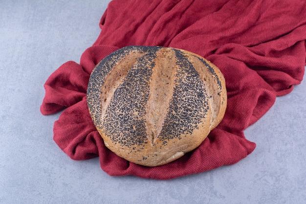 大理石の表面に黒ゴマでコーティングされたパンの塊の下にある一枚の布