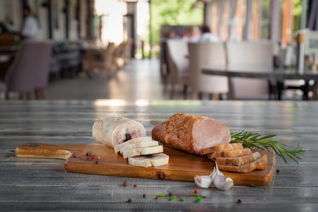 Кусок холодного отварного свиного филе, куриный рулет с черносливом, холодные закуски, чеснок, розмарин на деревянной разделочной доске