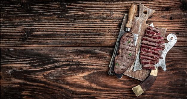 マーブルビーフミディアムレアの調理済みランプステーキを、木製のまな板の古い肉屋でお召し上がりいただけます。長いバナー形式、上面図。