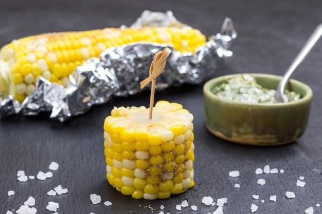 Кусок кукурузы на шпажке. вареная кукуруза в фольге. соус в миске. черный фон
