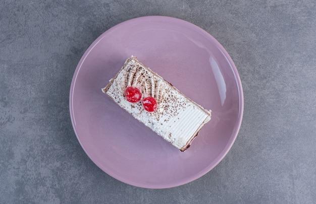 Кусок вкусного торта на фиолетовой тарелке.
