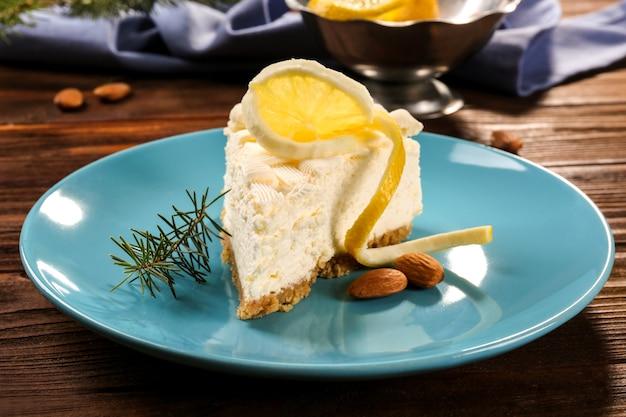 파란색 접시에 레몬을 넣은 맛있는 치즈 케이크 조각