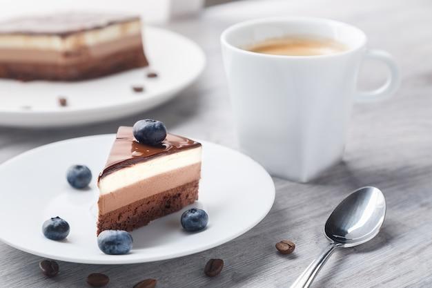 Кусок восхитительного шоколадного торта с суфле трех разных цветов в мягком фокусе.